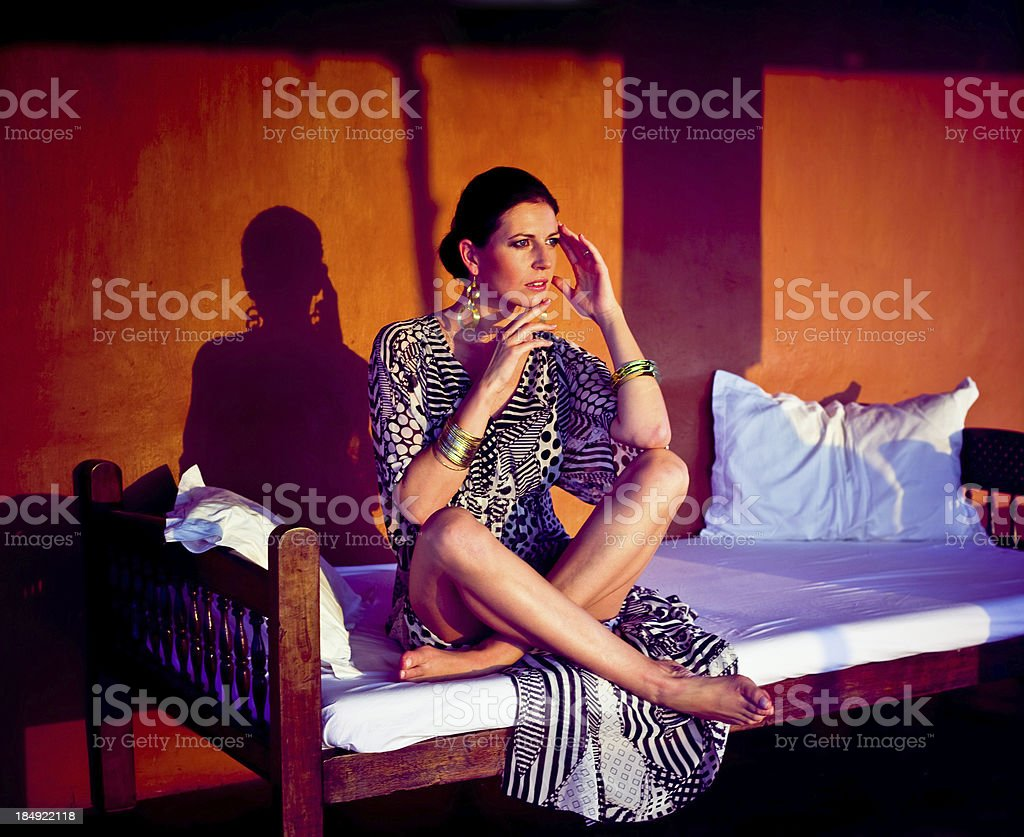 Relaxing woman at sunset Beautiful woman wearing summer dress and gold jewelry relaxing on a bed on veranda at sunset. 30-34 Years Stock Photo