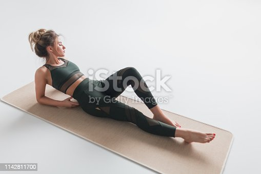 istock Relaxing woman in sportswear lying on mat 1142811700