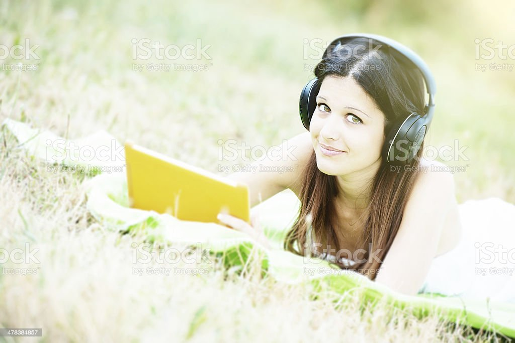 Relaxing young woman with digital tablet royalty-free stock photo