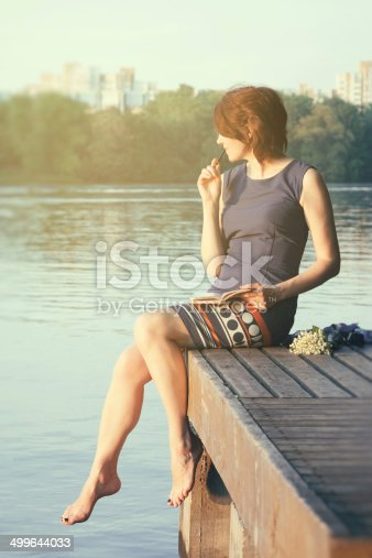 611108702 istock photo relaxing young woman with notebook  in city park 499644033