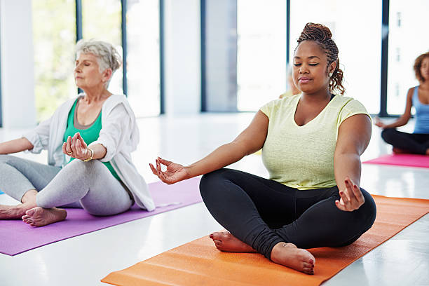 Release all your tension Shot of a group of women meditating indoors yoga class stock pictures, royalty-free photos & images
