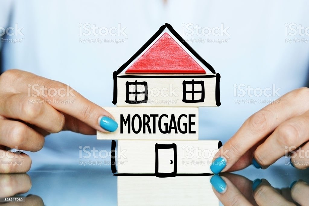 Release the mortgage of the property concept with young woman and house symbol on a table stock photo