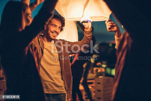 Group of friends launching a paper lantern at night.