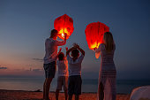 Releasing paper lanterns by the sea