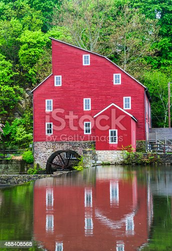 An old red mill is reflected in the mill pond above the  dam in Clinton, New Jersey.