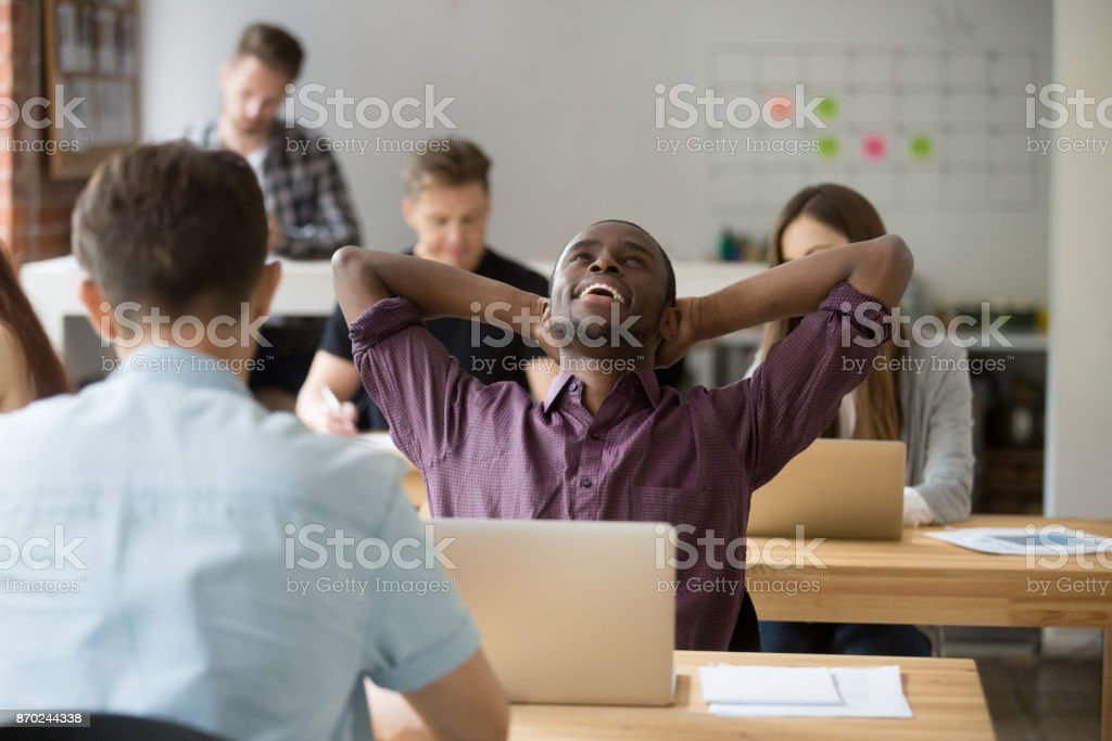 Relieved african american entrepreneur relaxing after finished work. stock photo