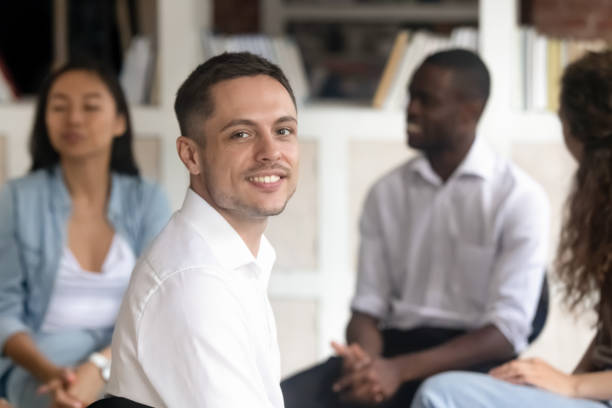 uomo caucasico sollevato in posa alla sessione di terapia di gruppo - assuefazione foto e immagini stock