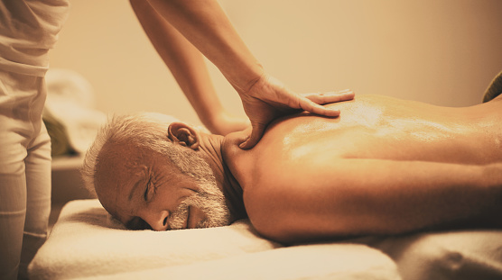 Side view of senior man lying on front on a massage table while enjoying a massage.