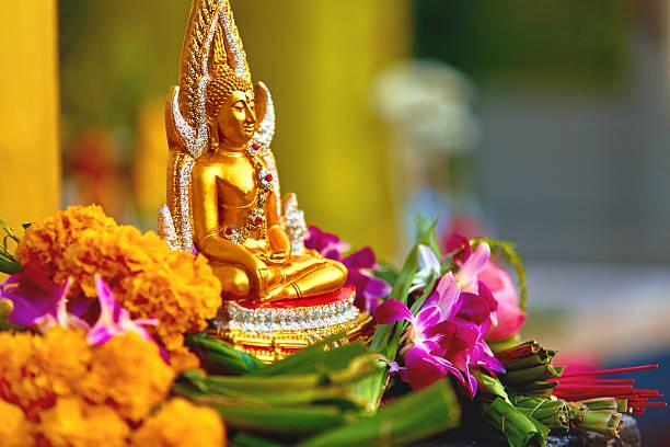 religion. buddha-statue mit blumen im tempel, thailand. buddhistische - lotus symbol stock-fotos und bilder