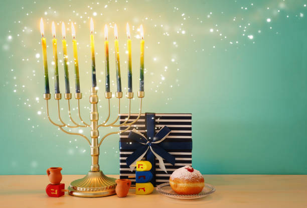 religion image of jewish holiday Hanukkah with menorah (traditional candelabra), spinning top and doughnut over wooden background stock photo