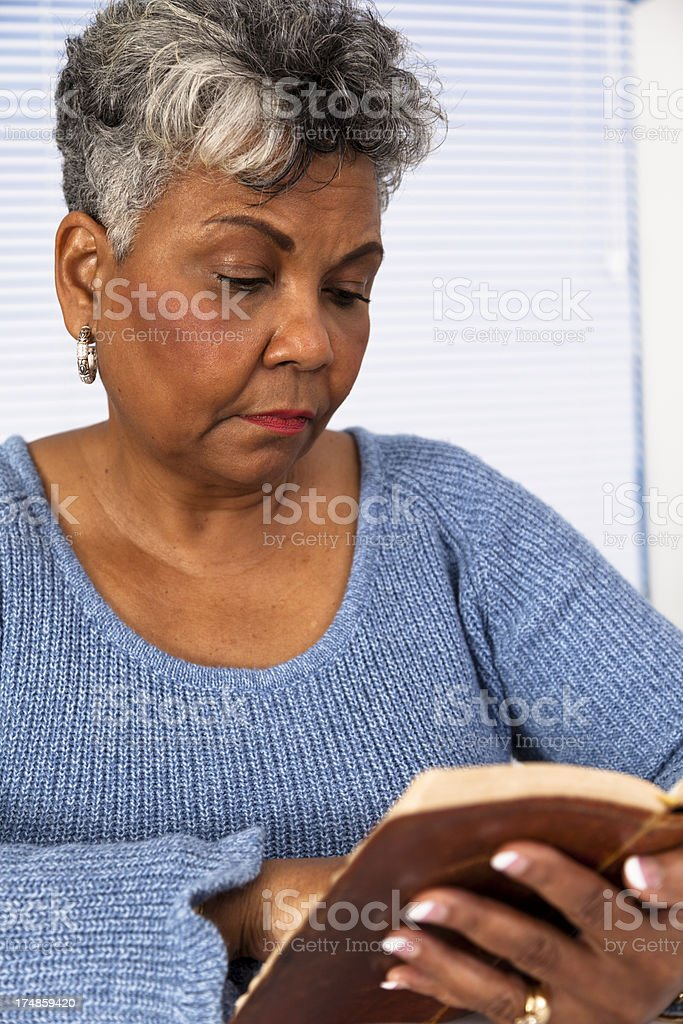 Religion:  Senior African decent woman reading Bible scripture royalty-free stock photo