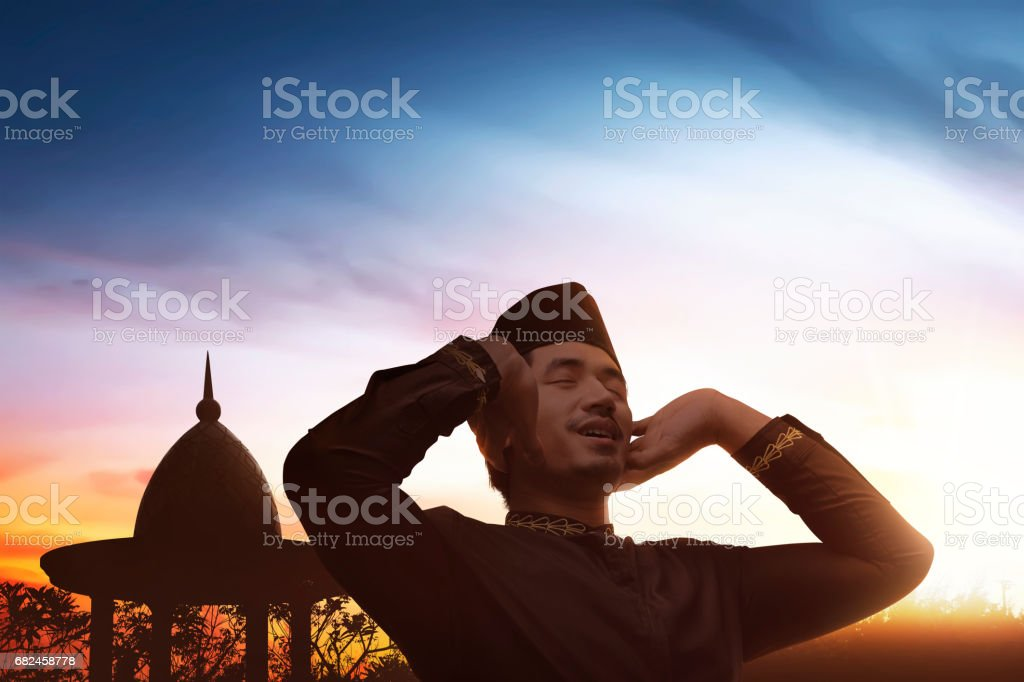 Religious asian muslim man in traditional dress praying to god royalty-free stock photo