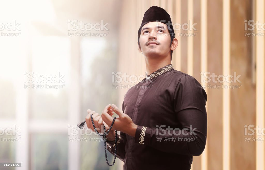 Religious asian muslim man in traditional dress using prayer beads stock photo