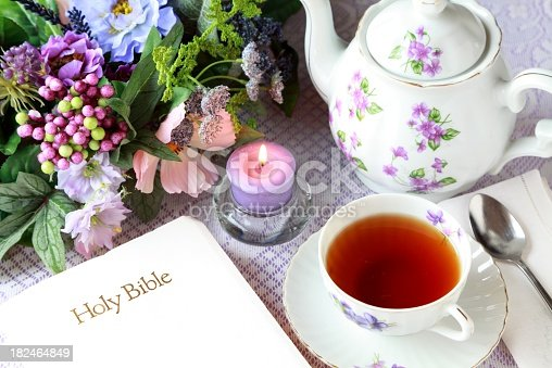 Lovely teapot and tea cup with violets with Bible, candle and flowers ready for meditation time.