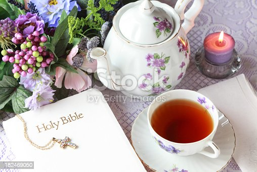 Lovely teapot and tea cup with violets with Bible and candle ready for meditation time.
