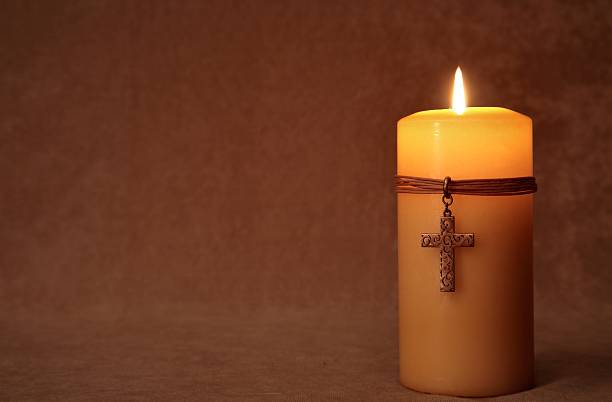 Religious: burning Candle with Cross and copy space Series stock photo