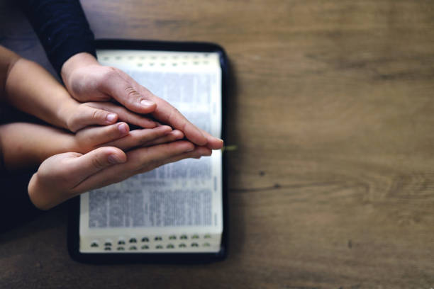 Religious Christian girl praying with her mother indoors Religious Christian girl praying with her mother indoors. Bible in background. Space for text place of worship stock pictures, royalty-free photos & images