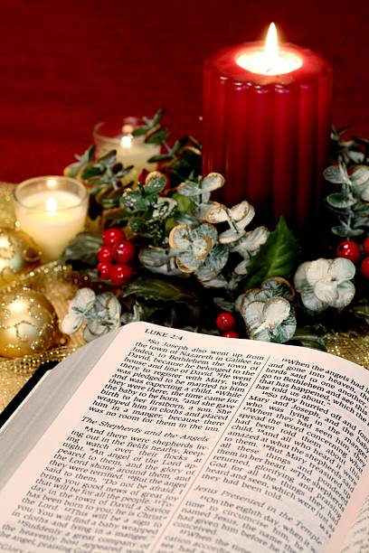 Religious: Christmas open to Bible scripture and red Candle stock photo