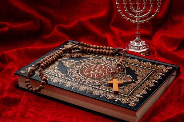 La convivencia religiosa, el monoteísmo y las religiones abrahámicas conviven en el tema conceptual de la paz con un Corán que representa el Islam, una cruz y un rosario que simbolizan el cristianismo y la menorah un símbolo del judaísmo - foto de stock