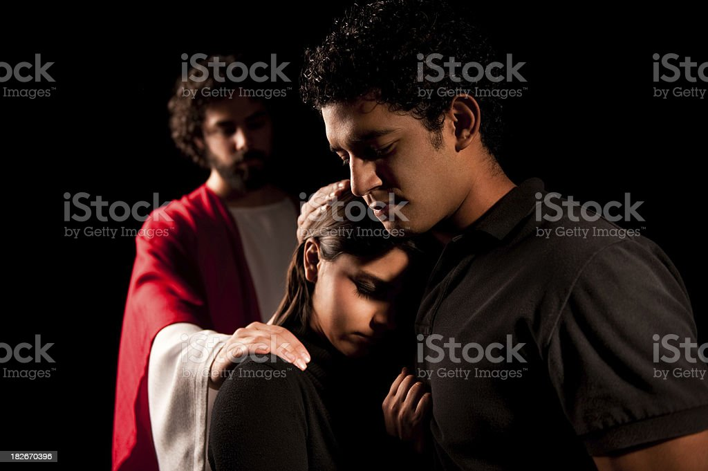 Religious couple with Jesus behind them in a dark room