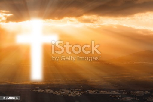 Christian cross glows against the rising sun. Religion, Easter, prayer concept