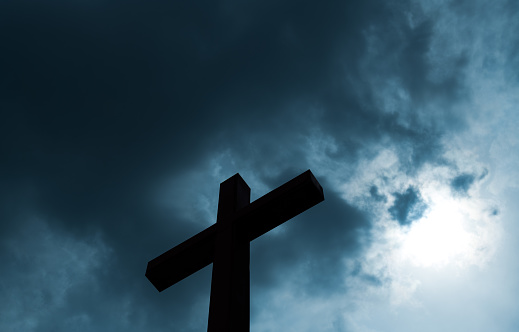 Religious cross under the cloudy sky.