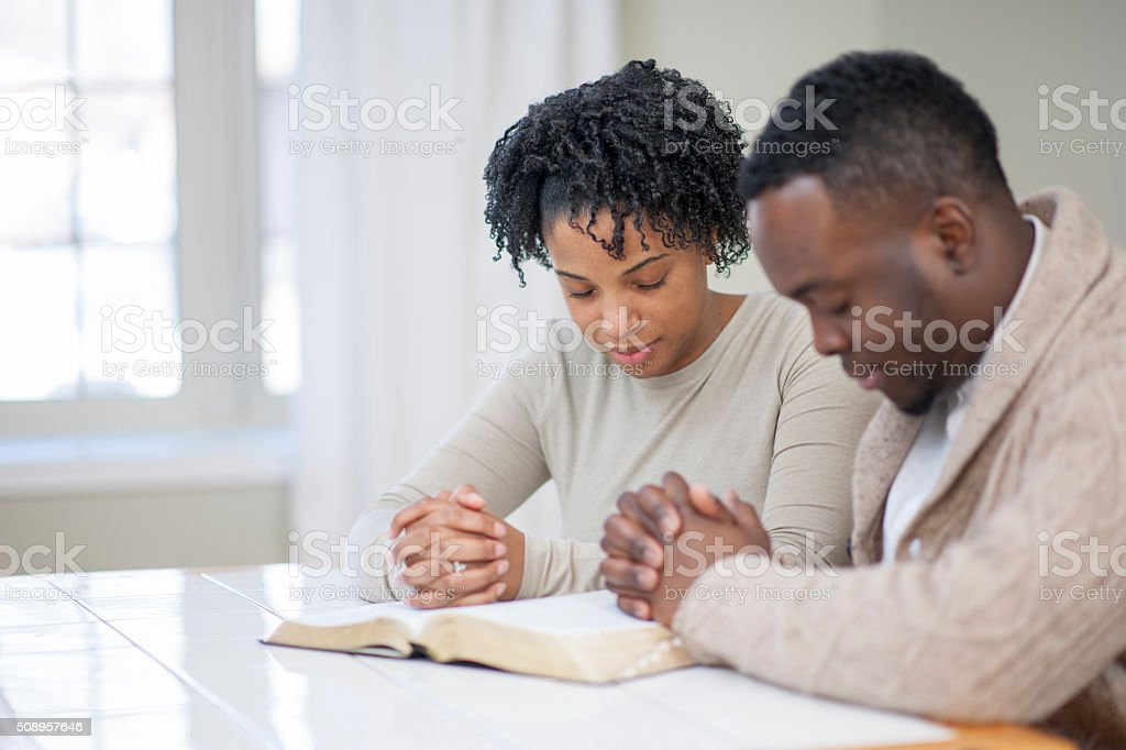 Religious Ethnic Couple Praying with a Bible stock photo