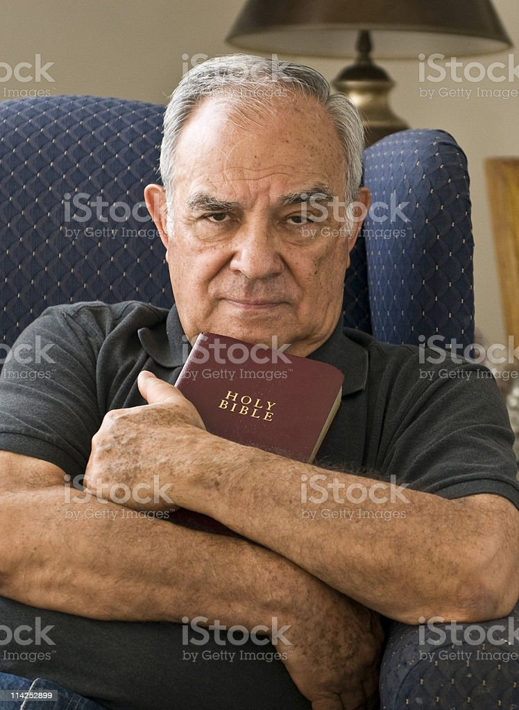 Religious Hispanic senior clutching bible royalty-free stock photo