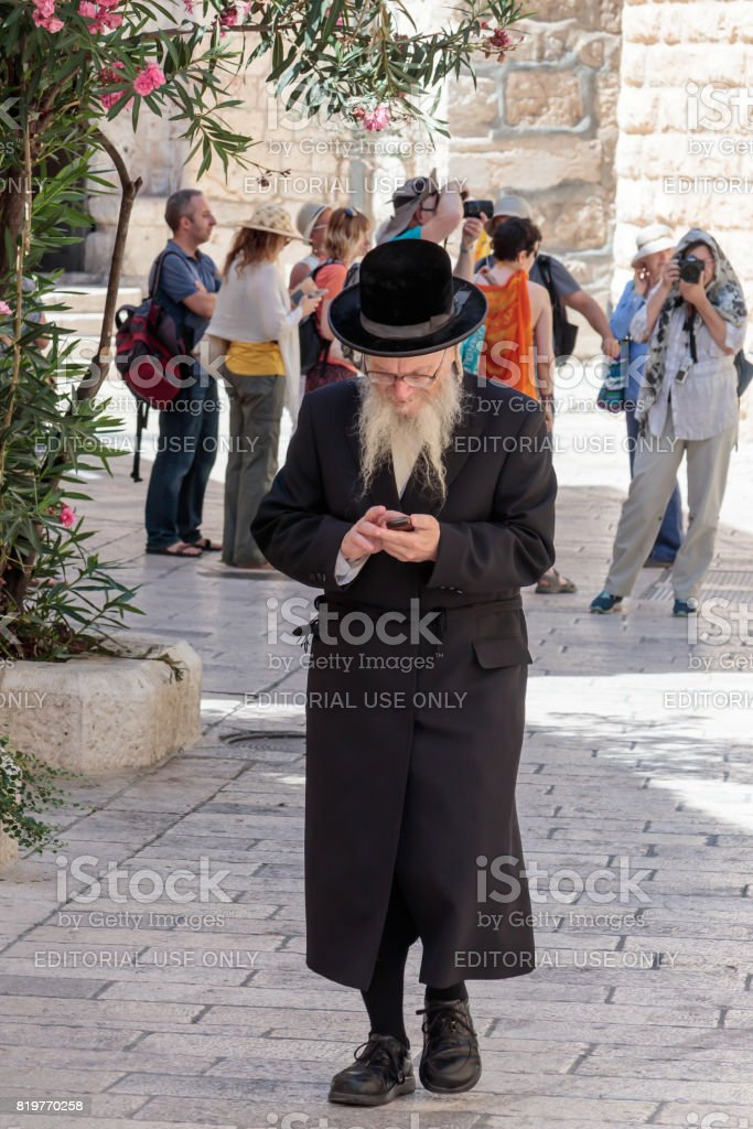 Religious Jew walks along the street and looks at his mobile phone in the old city of Jerusalem, Israel stock photo