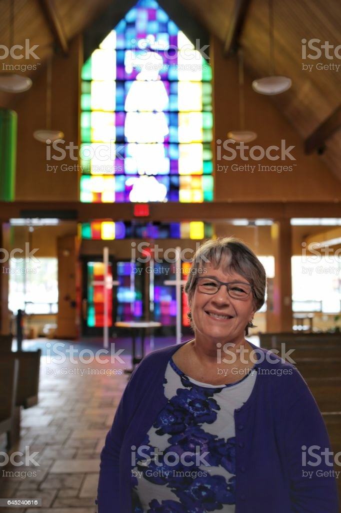 Religious Lay Minister Occupation Woman Standing in Catholic Church Aisle stock photo