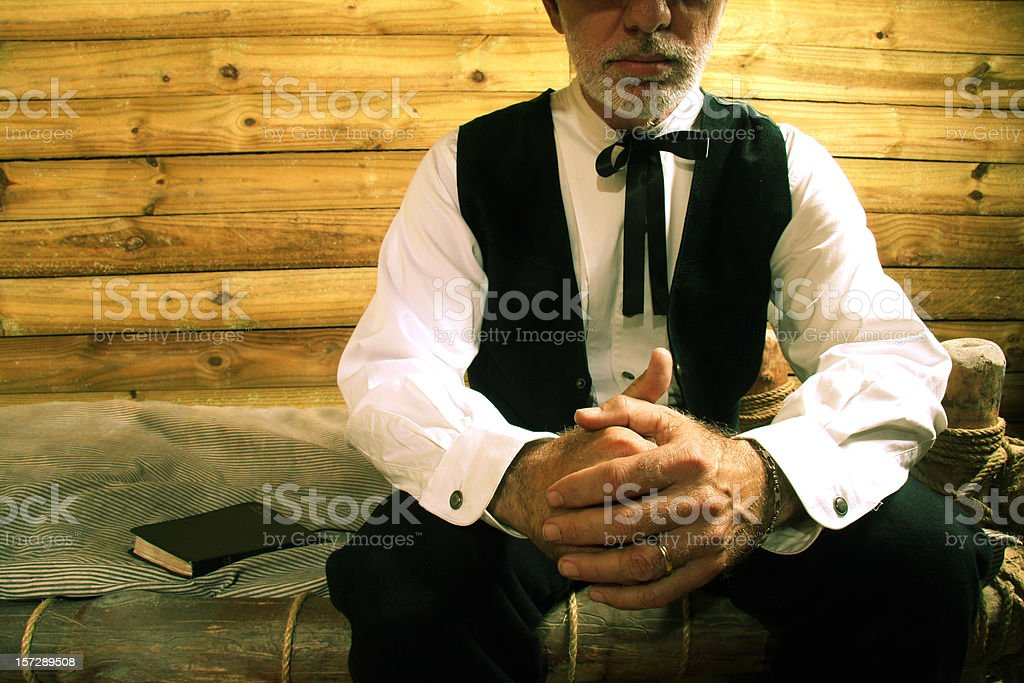 Religious man in a wooden cabin sat on a bed praying stock photo