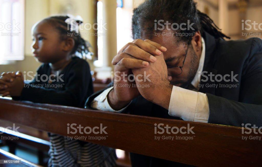 Religious man praying inside a church stock photo