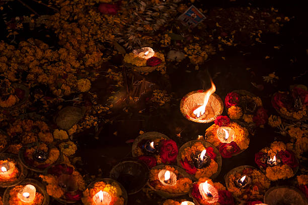 Religious offerings on River ganges and oil lamps, Varanasi, India Religious offering to holy Ganges river after sunset. As an offering, diya or oil lamps are put on small boats made of leaves and set afloat on the water.  dashashwamedh ghat stock pictures, royalty-free photos & images