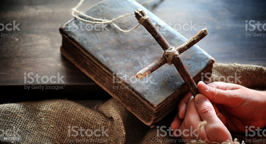 Religious old book on a wooden table. A religious cross tied wit stock photo