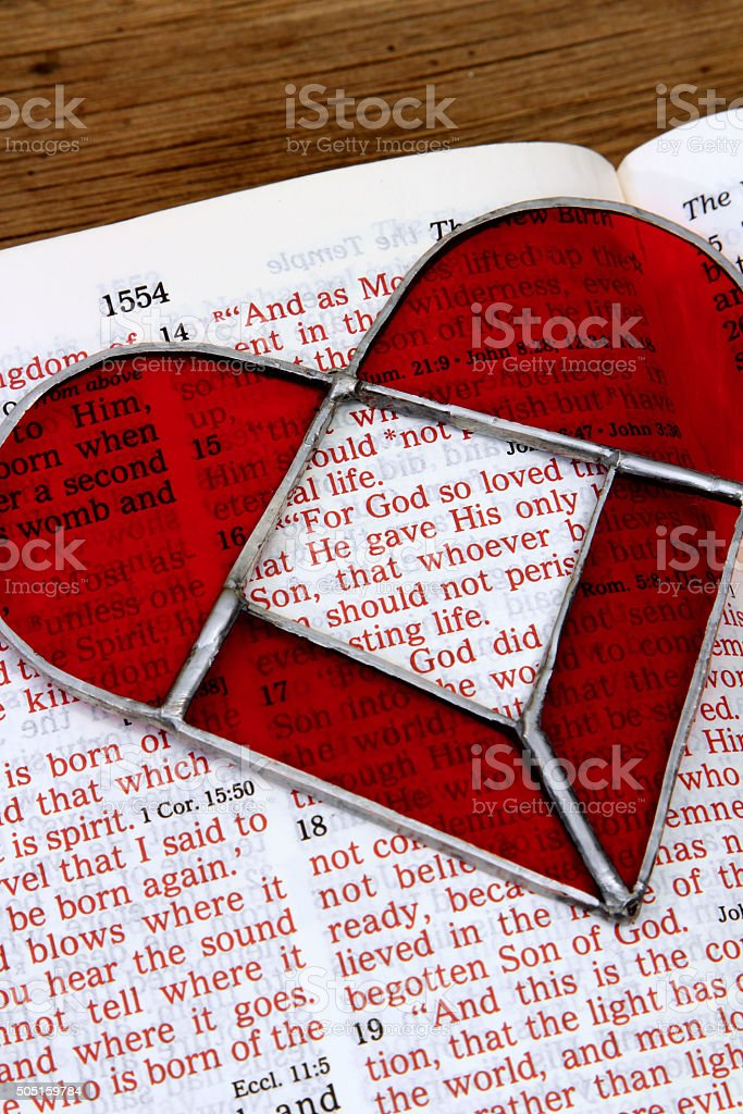 Religious: open Bible Scripture of John 3:16 with red heart stock photo