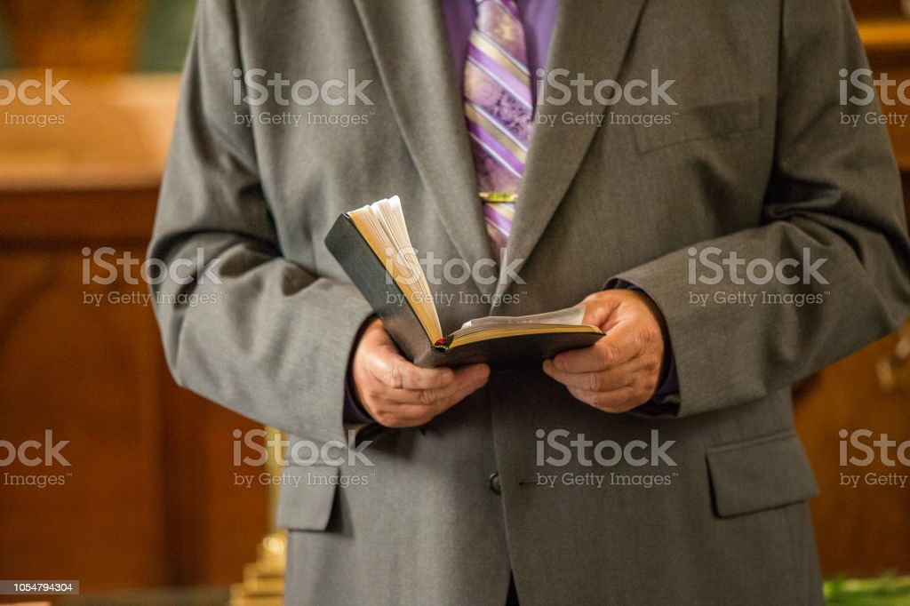 Religious Pastor Reading from Bible in Church - Royalty-free Adult Stock Photo