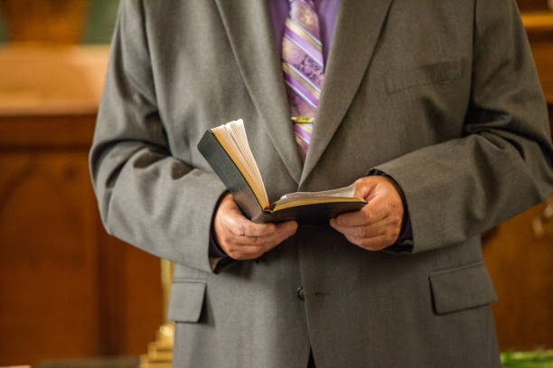 Religious Pastor Reading from Bible in Church stock photo