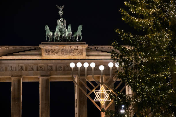 Religious symbol and shiny Christmas tree in front of Brandenburg Gate neoclassical monument in Berlin Germany. Night cityscape with Jewish Hanukah decorations and traditional Christmas decorations stock photo