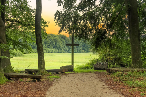 A religious wooden cross in a small forest in Europe.