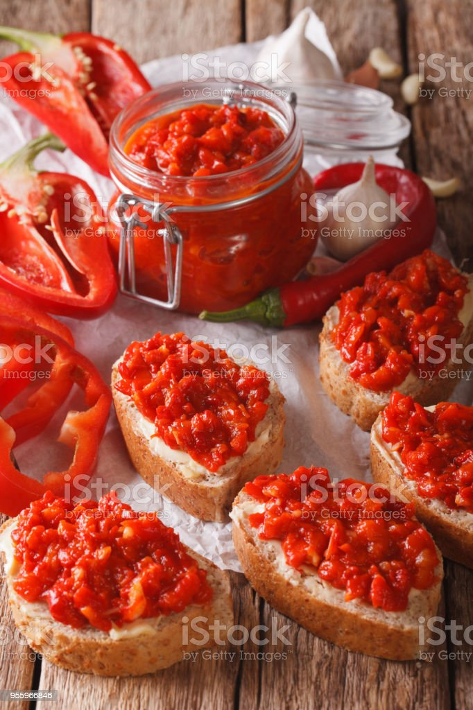 Relish (Ajvar) of Roasted Red Bell Peppers on toast slices close-up. Vertical stock photo