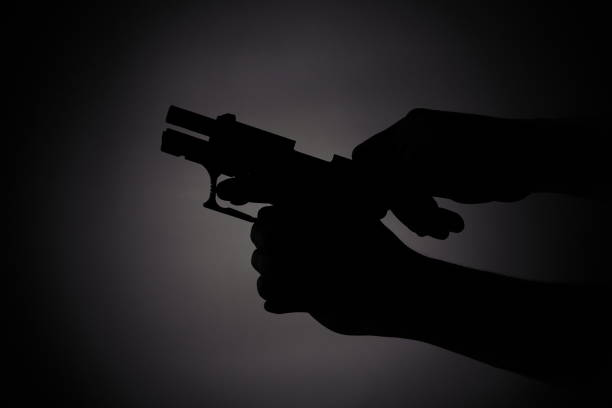 reloading the gun in the dark black silhouette of a male reloading a gun in the dark ambush stock pictures, royalty-free photos & images