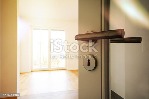 istock Relocation Moving to new apartment - Door to modern living room, new construction property 871409854