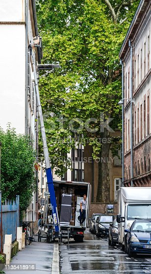 Strasbourg, France - Sep 12, 2017: Young male worker waiting for the hydraulic elevator boom to deliver another package during home relocation
