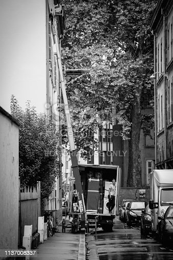 Strasbourg, France - Sep 12, 2017: Young male worker waiting for the hydraulic elevator boom to deliver another package during home relocation black and white