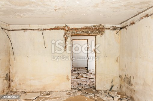 Remains of abandoned damaged and destroyed house interior by grenade shelling with collapsed roof and wall in the war zone selective focus