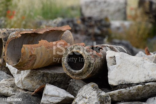 The remains of ancient ceramic pipes from the water supply. Prefabricated sections of ceramics from which the pipeline was assembled.