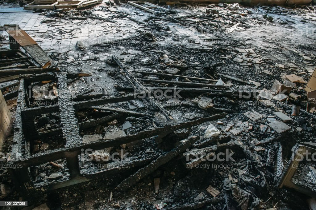 Remains of burnt wooden furniture on the floor of building after...