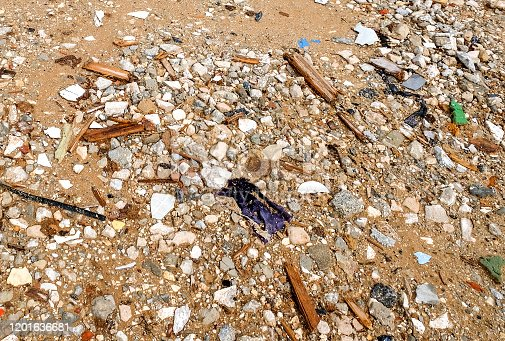 Remains of construction debris at a construction site with sand, gravel, fragments of tiles, plastic and metal