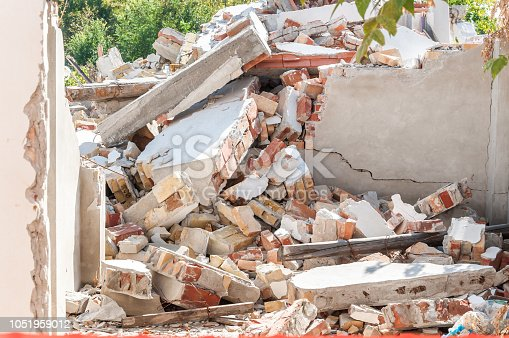 istock Remains of hurricane or earthquake disaster damage on ruined old house with collapsed roof and walls on the pile 1051959012