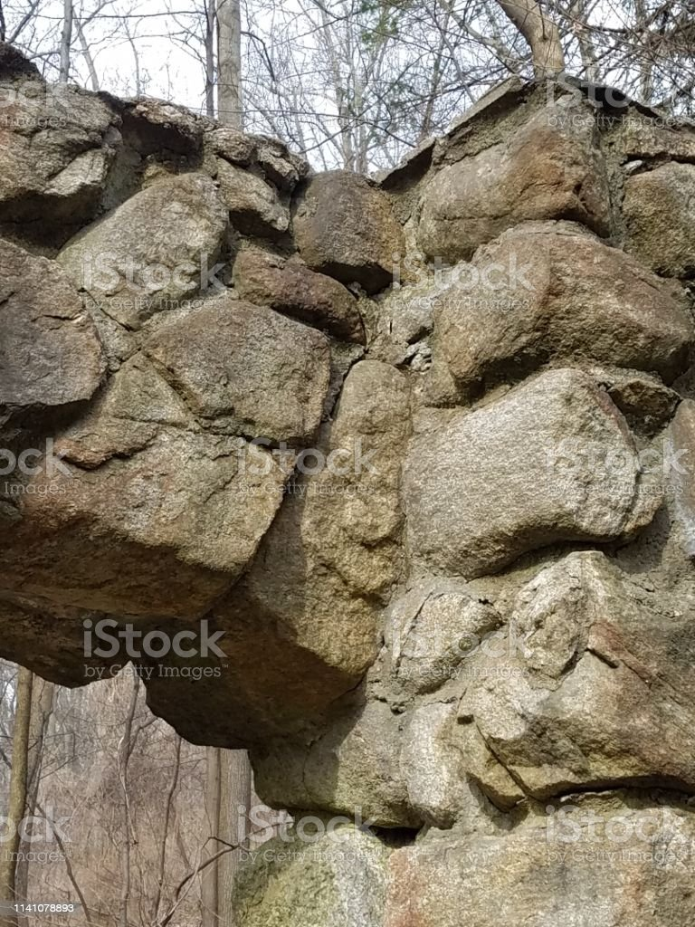 Remains of stone wall and portico arch at ruins stock photo